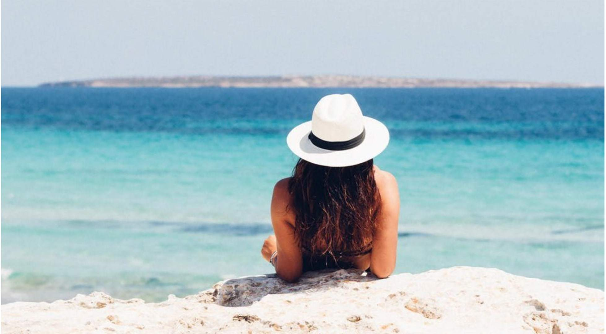 Photo of a woman, wearing a hat, relaxing on the beach looking out on the ocean.