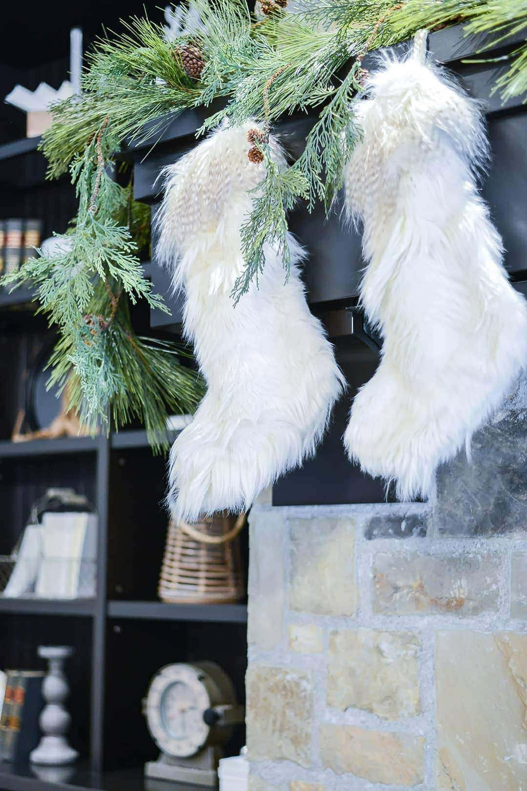The fireplace is beautifully adorned with fresh greener and fur stockings.