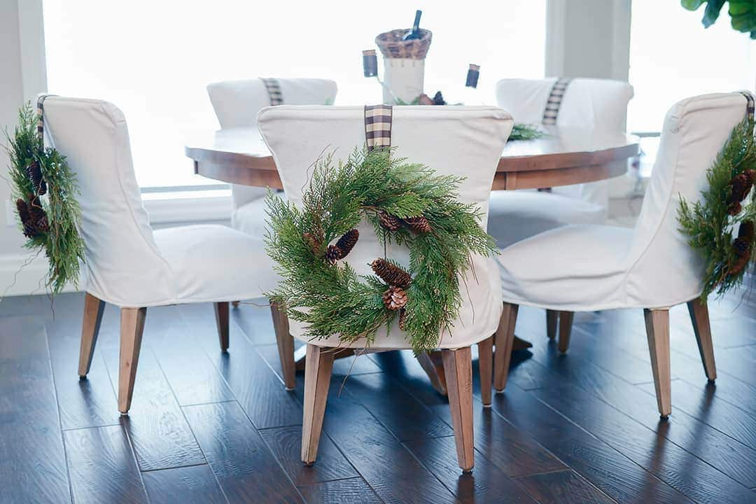 Wreaths are hung on each chair using warm earthy ribbon.