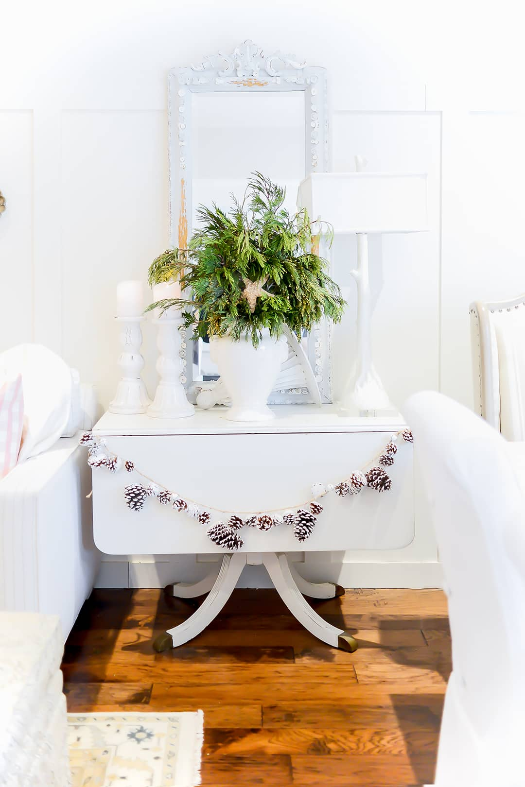 A small table beautifully swagged with a flocked acorn garland white chunky candles, a white lamp and a large pretty white vase of fresh greenery enhanced with baby wooded stars.