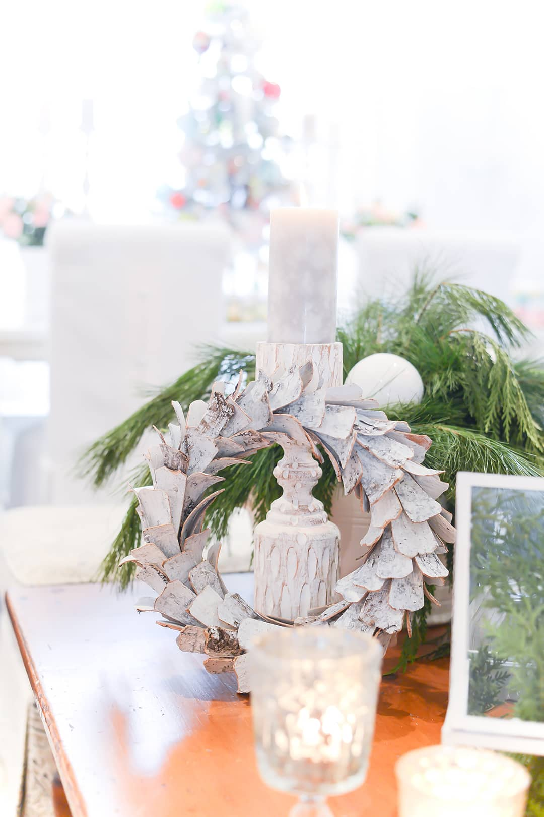 A pine coffee table close up image of flickering white candle sticks, a white birch bark wreath and greenery.