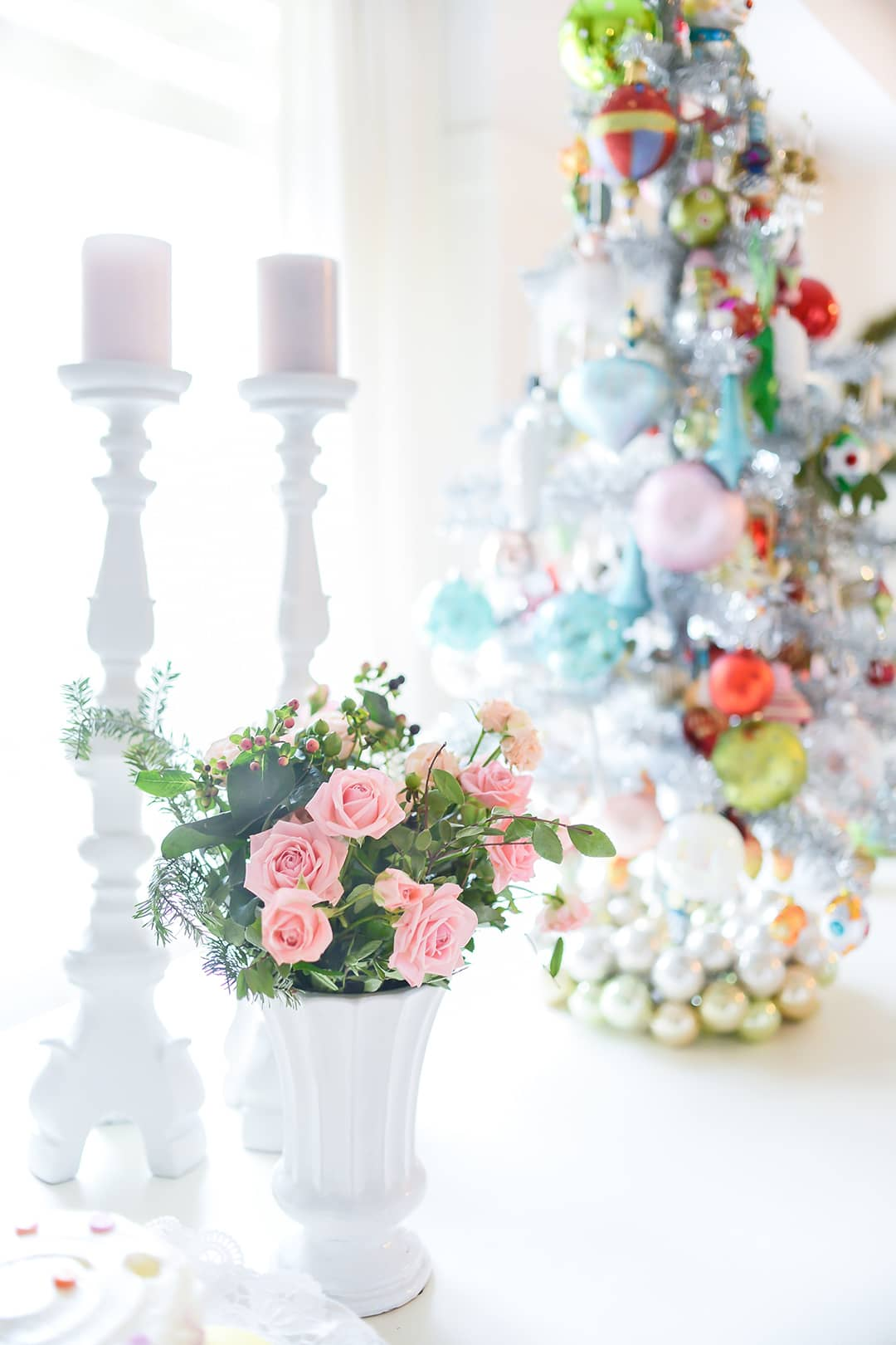 Close up image of a Christmas tablescape with table top tree, tall candle stick and fresh mini pink roses.