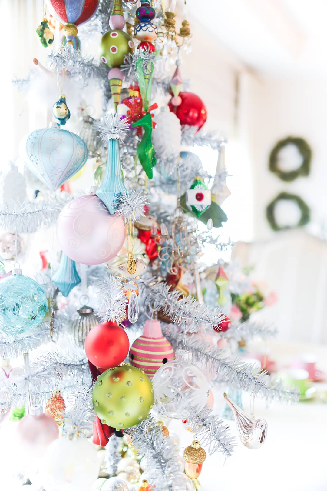 Close up image of heavily flocked tree adorned with colourful Christmas ornaments and bobbles in hot pin, lime green, pale pink, turquoise and gold.