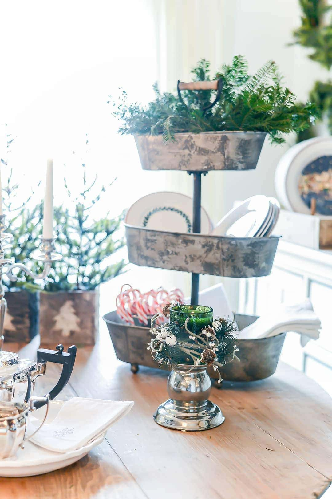 A wooden table is dressed with rustic tin accents and fresh greenery. Including a 3 tiered serving tray of rustic metal holding candy canes and greenery as well as mini Christmas trees in wooden rustic pots.