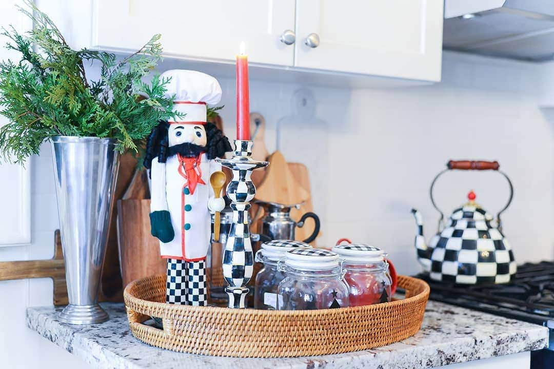 A wicker wooden serving tray accented with black and white checkered items including a Nutcracker, candlestick and glass jar lids.