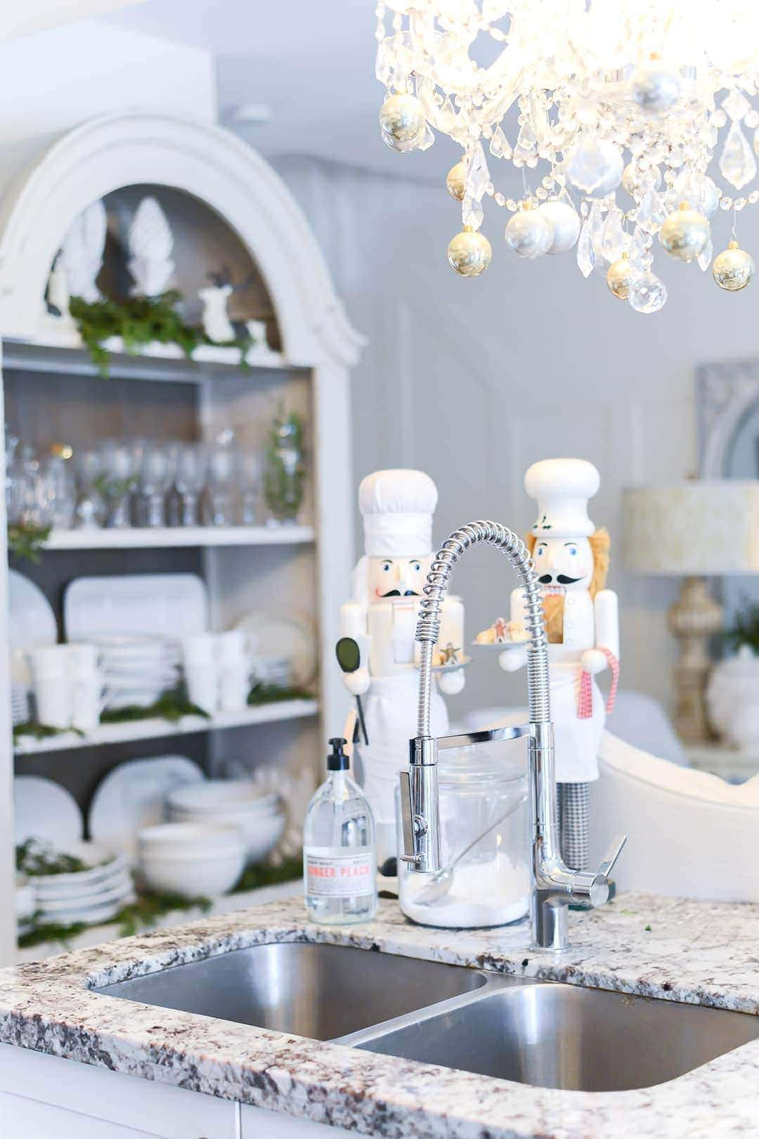 2 white Nutcrackers adorned the counter top and sink area, with large cabinet and crystal glassware in the background.