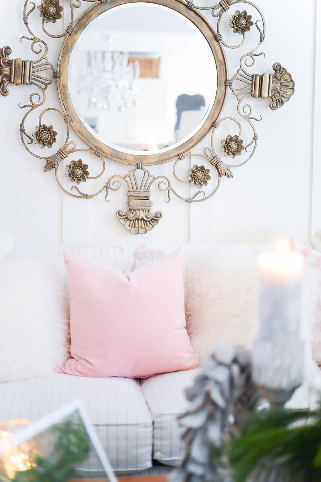 Sofa showcasing pastel pink pillows, white fur pillows, along with a beautiful gold hanging mirror above.