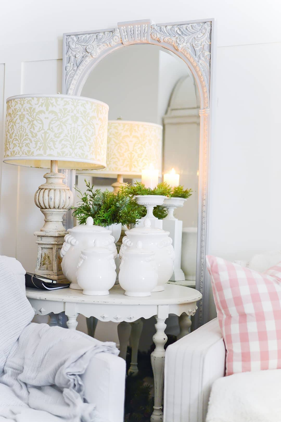 White wood painted side table with a collection of white porcelain urns, concrete lamp with a pretty damask shade accented by a white wood mirror, candles and greenery.