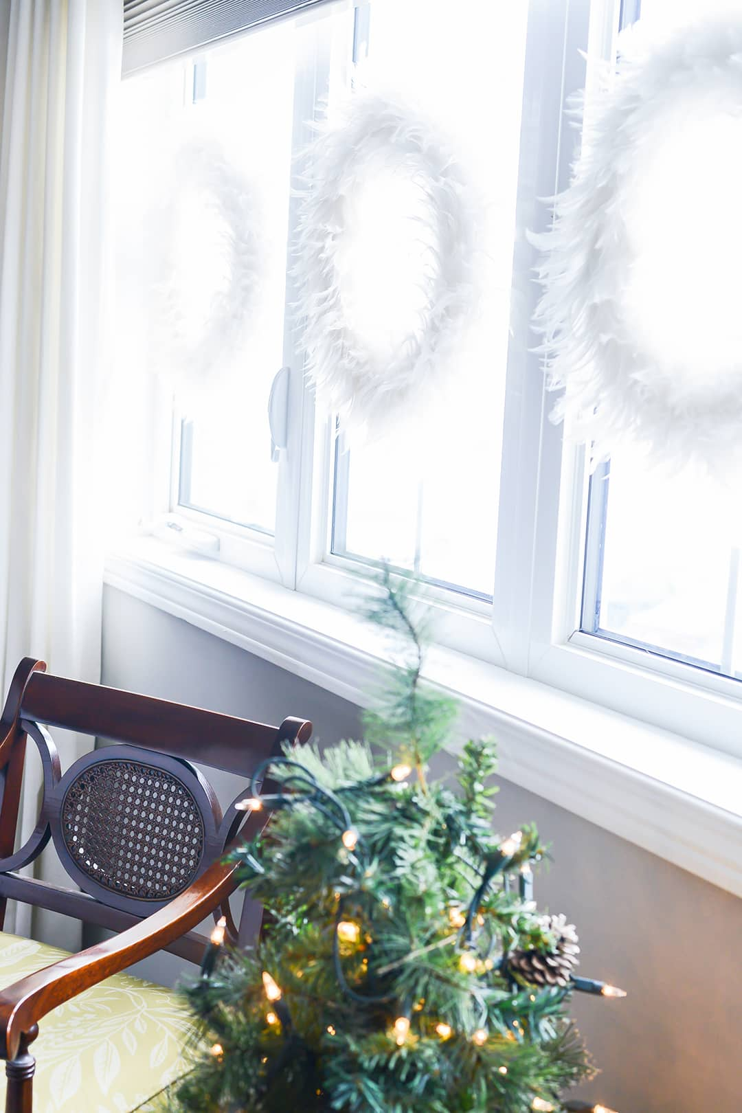 Master bedroom has fluffy white feather wreaths hanging along all 3 windows, along with an accent chair and table top Christmas tree on a small side table.