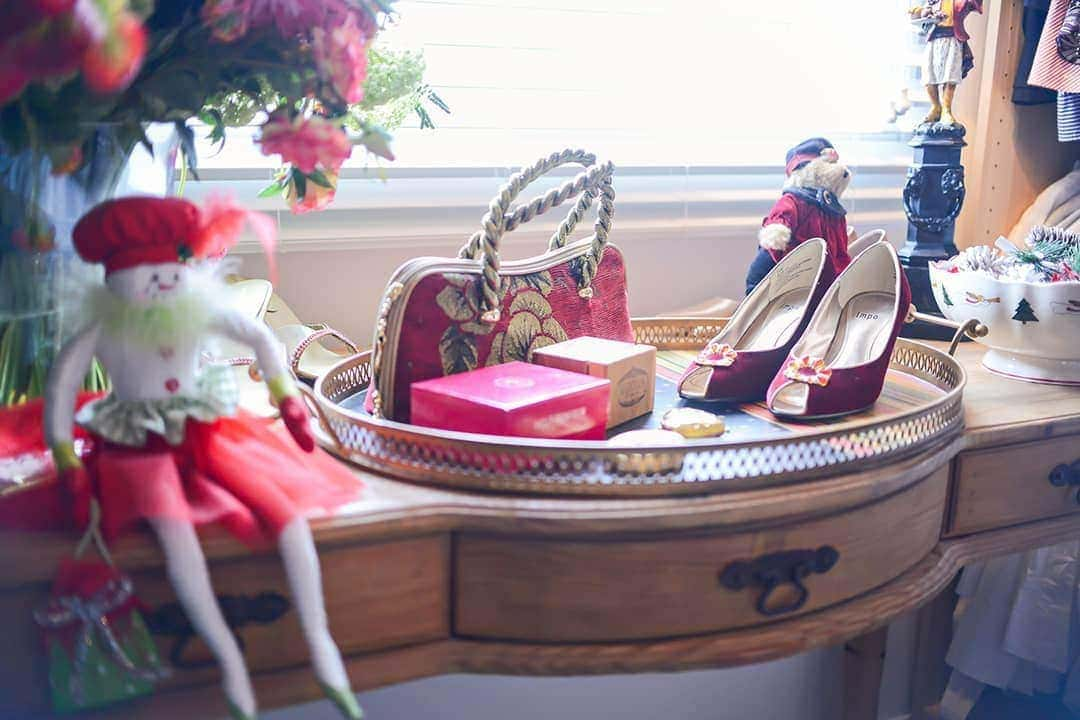 Master closet antique dressing table, adorn with red shoes, pretty red purse and a Christmas Elf.