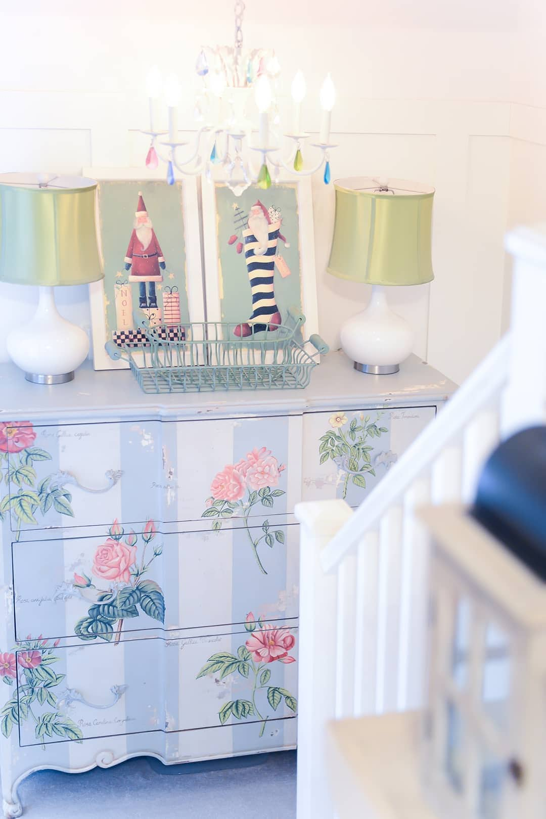 Hand painted chest with white side lamps with a lime green satin shade along with 2 whimsical framed Santa Claus prints.