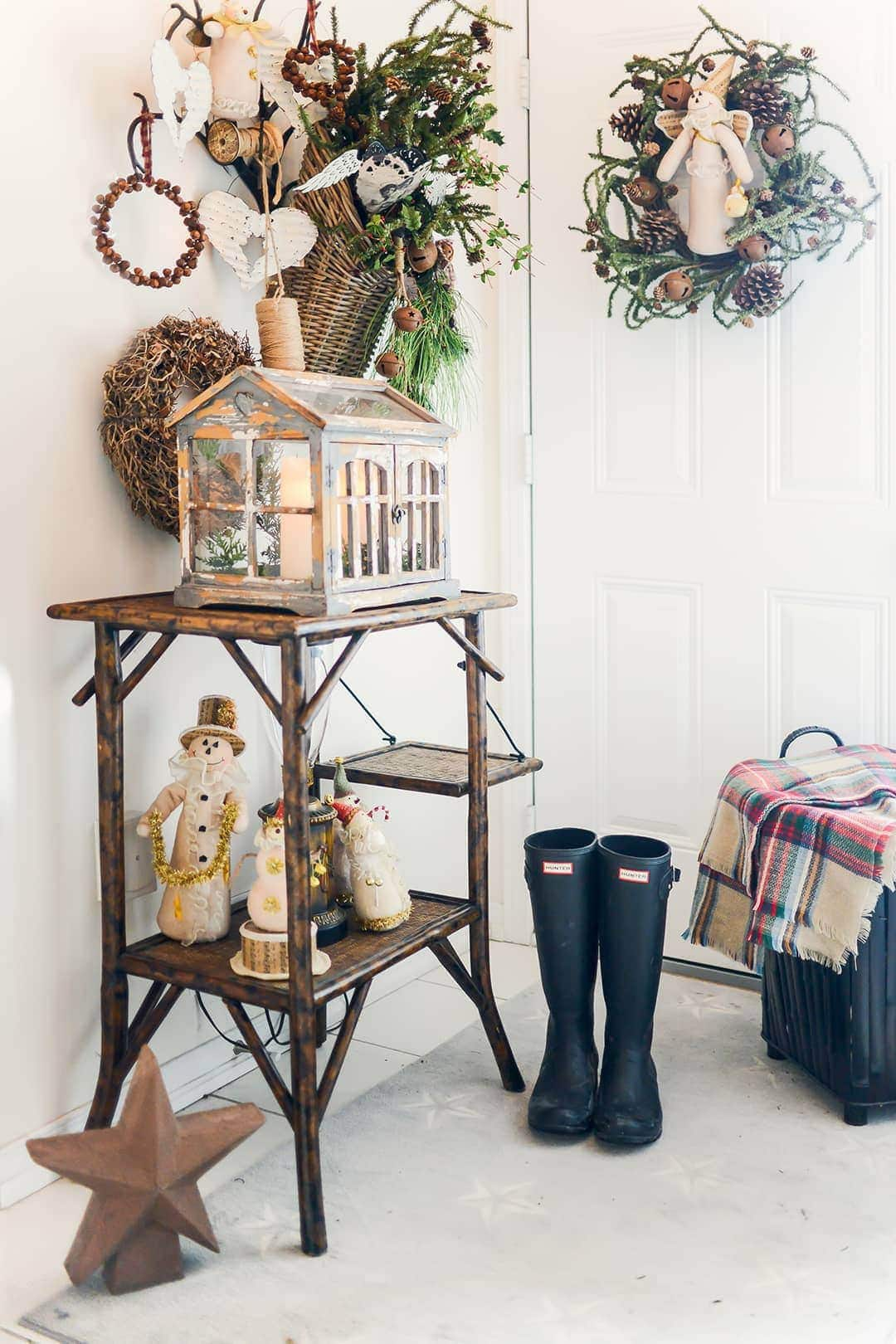The home foyer adorned with wooden accents of winter snowmen, wreaths , plaid throw and Hunter rain boots.