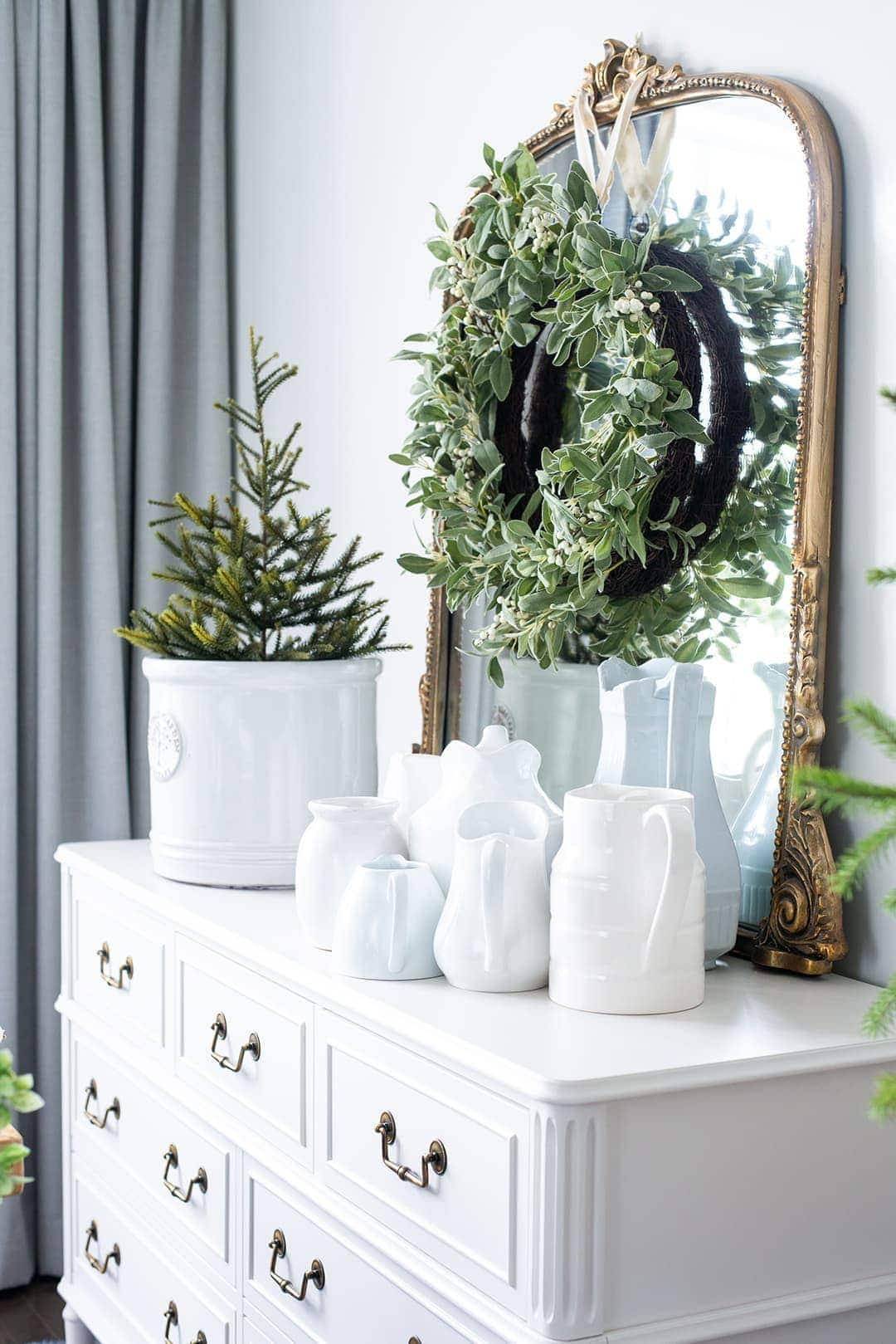 Painted cabinet, oversized mirror, adorned with hanging wreaths, white milk jugs and a real mini Christmas tree.